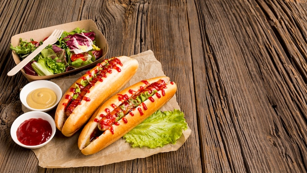 Hot dogs and small bowls with spices Free Photo