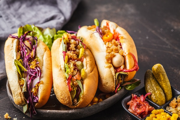 Hot dogs with assorted toppings on a dark background, top view. Premium Photo