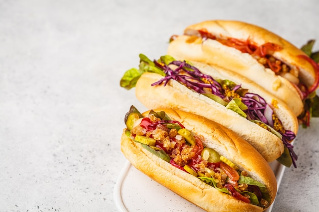 Hot dogs with assorted toppings on a white background, top view. Premium Photo