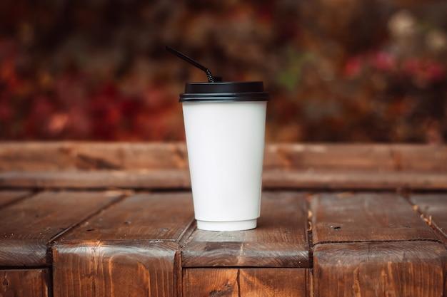 Горячий напиток в белом бумажном стаканчике с соломинкой на деревянной скамейке. солнечный осенний день. мокап для дизайна Premium Фотографии