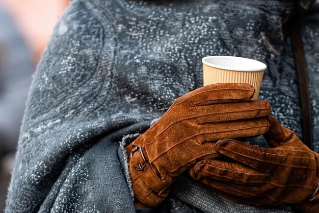 Горячий напиток в бумажном стаканчике в руках с перчатками Premium Фотографии