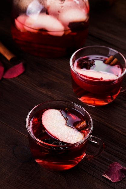Hot drink with hibiscus red tea with apple, cinnamon and anise in glass teapot and two glasses Premium Photo