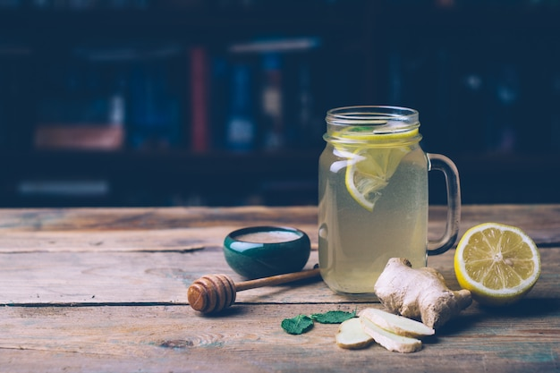 Hot drink with honey, lemon and ginger on wooden background Premium Photo