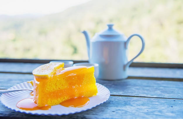 Hot eat cup and orange cake with green nature background Free Photo