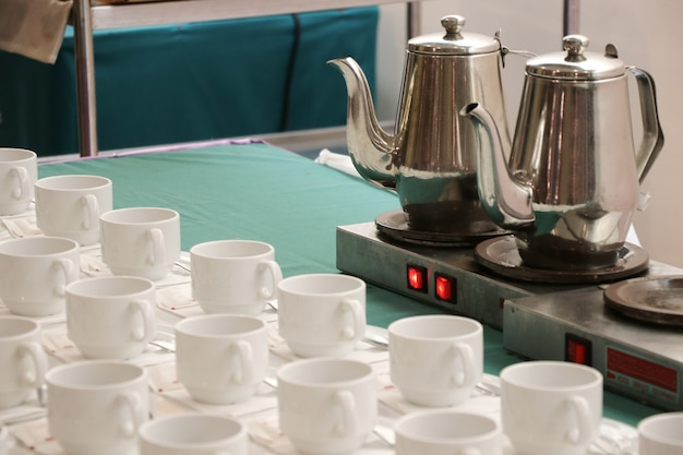 Hot electric kettle with cups puting on green fabric at hotal table for morning day Premium Photo