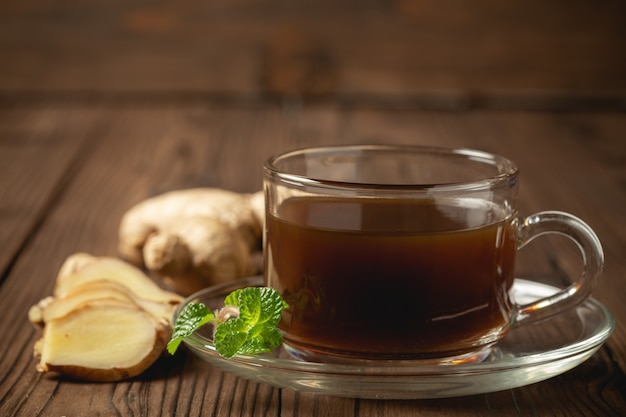 Hot ginger juice and ginger sliced on wooden table. Free Photo