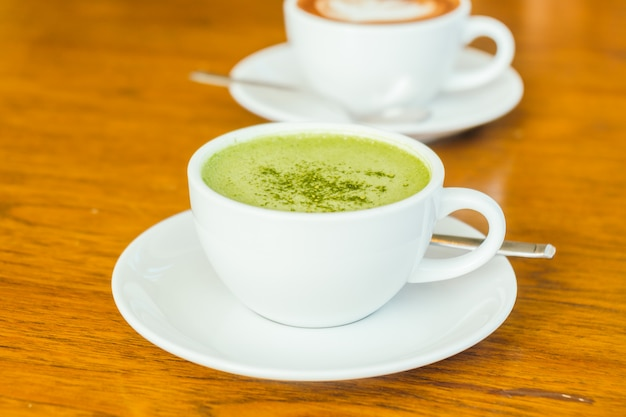 Hot green matcha latte in white cup Free Photo