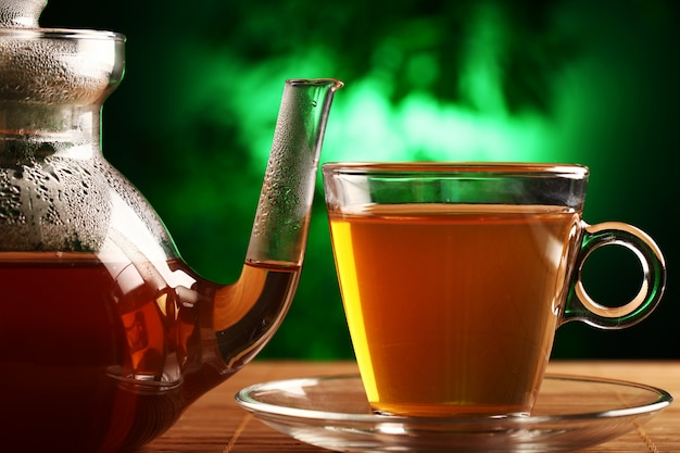 Hot green tea in glass teapot and cup Free Photo