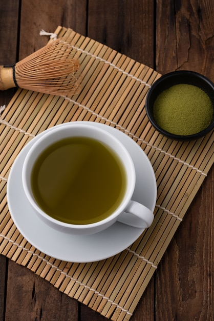 Hot green tea with powder on wood Premium Photo