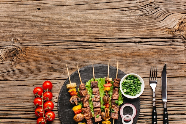 Hot grilled kebab skewers with vegetable on black slate over wooden surface Free Photo