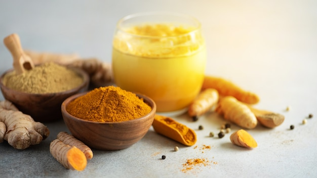 Hot healthy drink. turmeric latte, golden milk with turmeric root, ginger powder, black pepper over grey background. Premium Photo