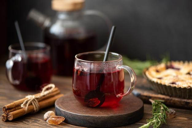 Горячий чай из гибискуса с корицей и сахаром на деревянном столе Premium Фотографии