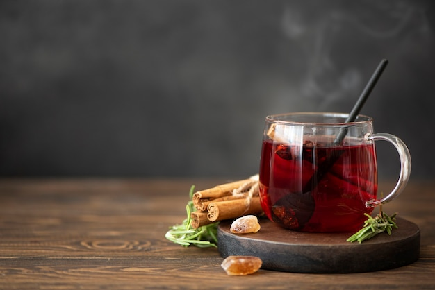 Hot hibiscus tea with cinnamon and sugar on a wooden table Premium Photo
