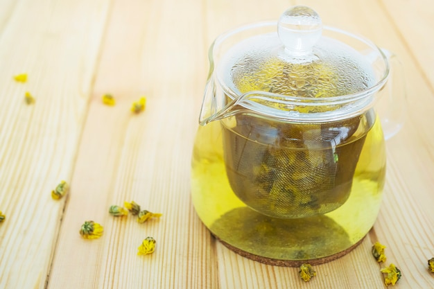 Hot jar of chrysanthemum ready for drinking on wooden table Free Photo