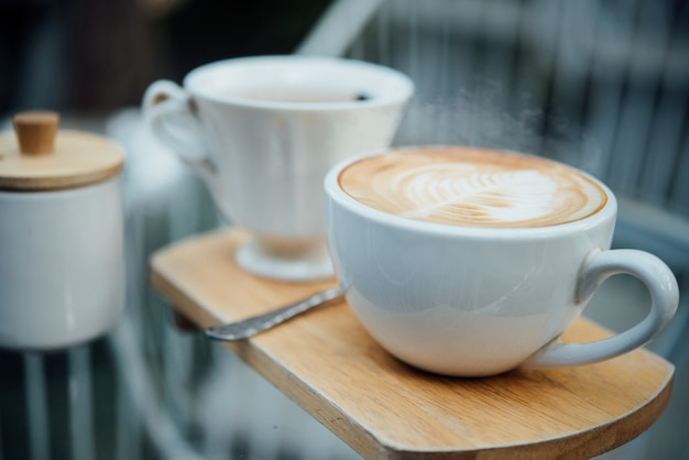 Hot latte art in coffee cup on wood table in coffee shop Free Photo
