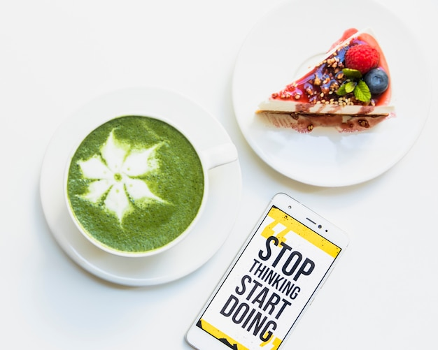 Hot matcha green tea cup; cheesecake and cellphone with message on screen over white backdrop Free Photo