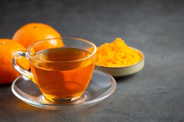 テーブルの上のホットオレンジティーとフレッシュオレンジ 無料写真