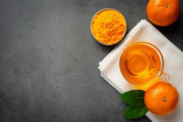 Tè arancione caldo e arancia fresca sul tavolo Foto Gratuite