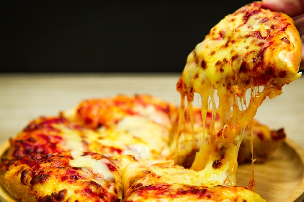 Hot pizza slice with melting cheese on a table in restaurant pizza. Premium Photo