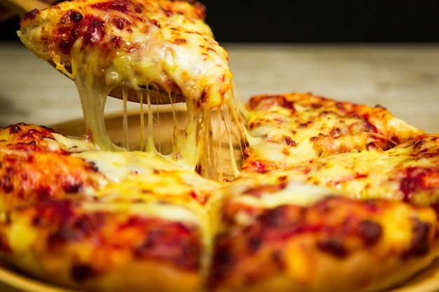 Hot pizza slice with melting cheese. Premium Photo