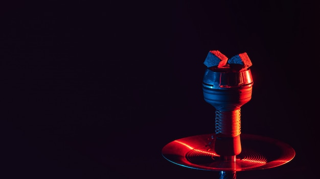Hot red coals for hookah shisha in a ceramic metal bowl with red blue neon lighting Premium Photo
