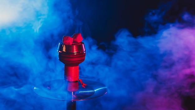 Hot red coals for hookah shisha in a metal bowl with smoke Premium Photo
