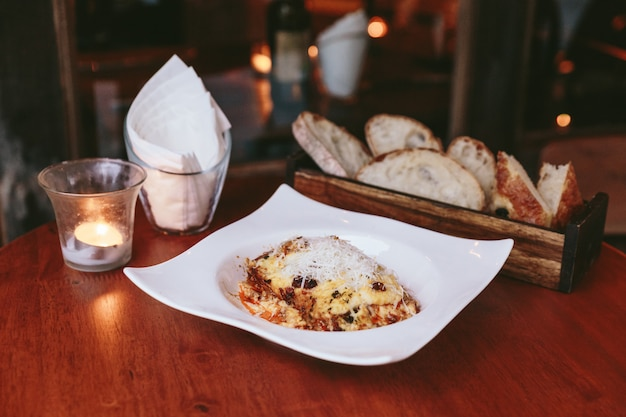 Hot served lasagne topping with mozzarella cheese served with sliced bread in wooden box. Premium Photo