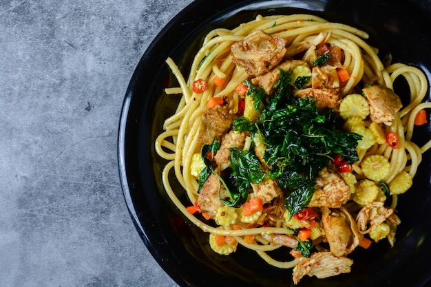 Hot and spicy chicken spaghetti, topping with crispy sweet basil and sliced baby corn Premium Photo