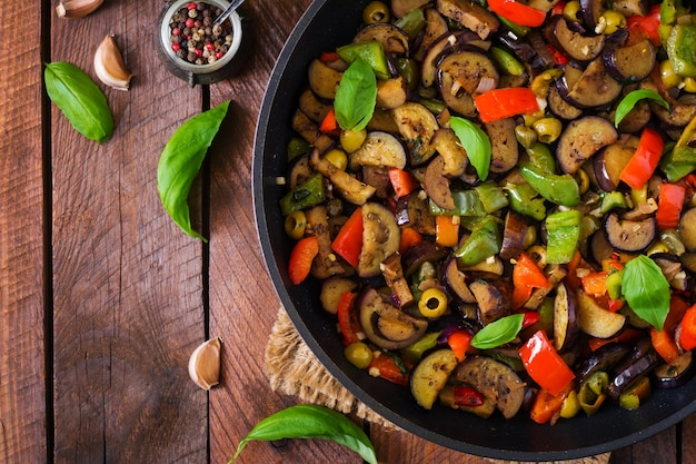 Hot spicy stew eggplant, sweet pepper, olives and capers with basil leaves. top view Free Photo