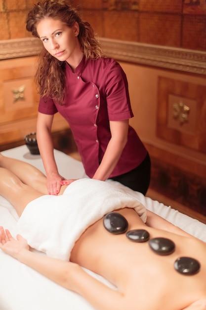 Hot stone massage therapy Premium Photo