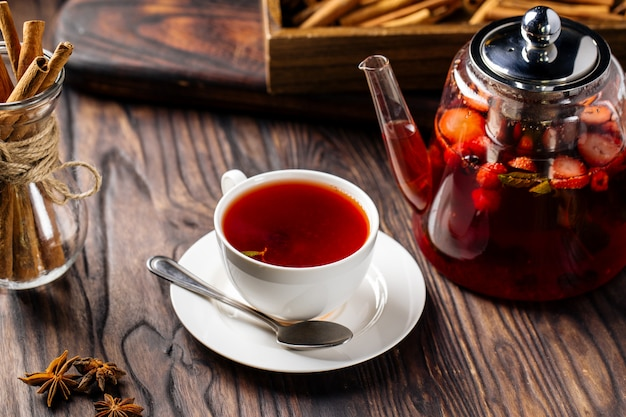 Hot sweet berry tea in white cup and glass teapot Premium Photo