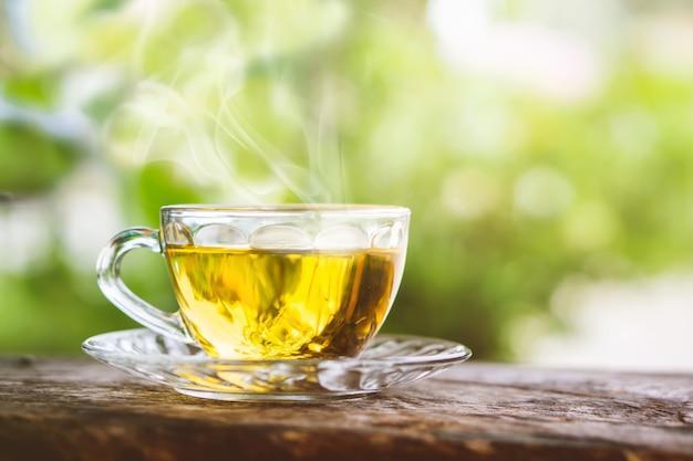 Чашка горячего чая на деревянном столе утром Premium Фотографии