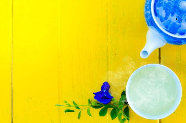 Hot tea cup and teapot floral design on yellow background, time of tea break Premium Photo