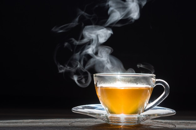 Hot tea in glass teapot and cup with steam on wood background Premium Photo