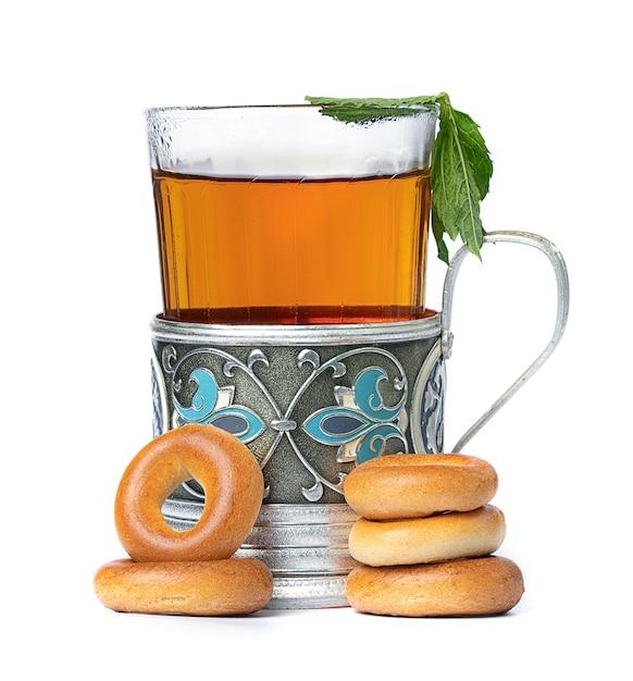 ガラスの熱いお茶と白いスペースにベーグルとカップ Premium写真