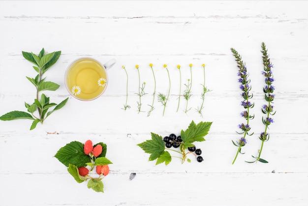 Горячий чай на деревянном белом фоне, ингредиенты для приготовления натурального травяного чая Premium Фотографии