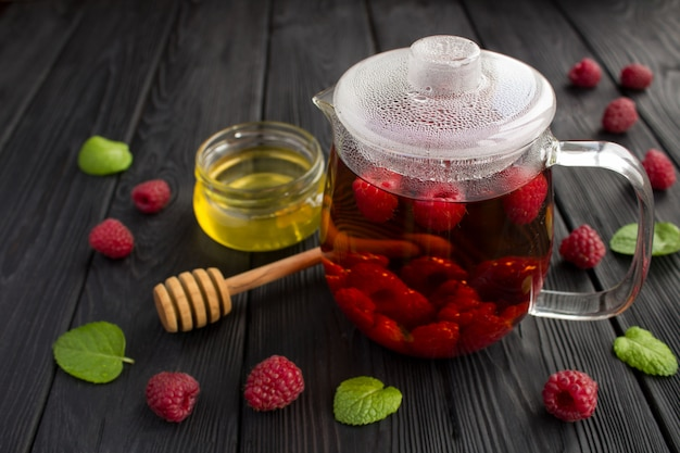 Hot tea with raspberries, honey and mint Premium Photo