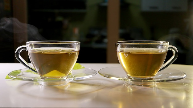 Hot tea with smoke in the glass cup with saucers. foods and drink concept. Premium Photo