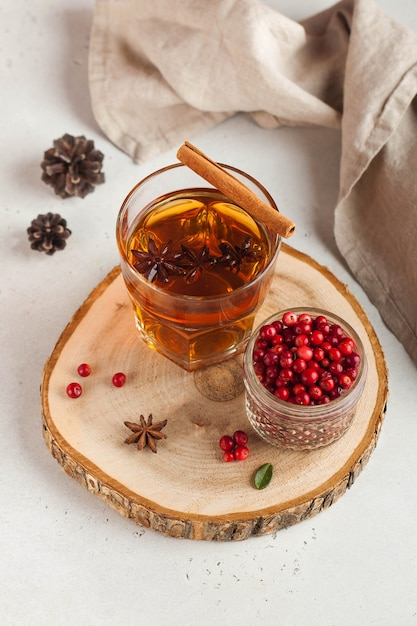 Hot tea with spices, apple and cranberry berries in a transparent glass mug on a wooden stand. Premium Photo