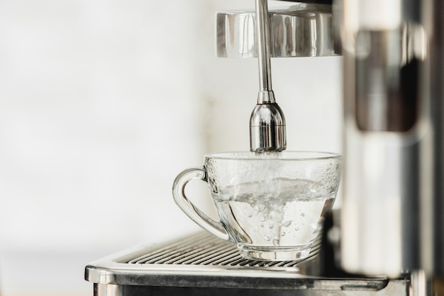 Hot water from coffee maker machine flowing into the cup for americano making Premium Photo