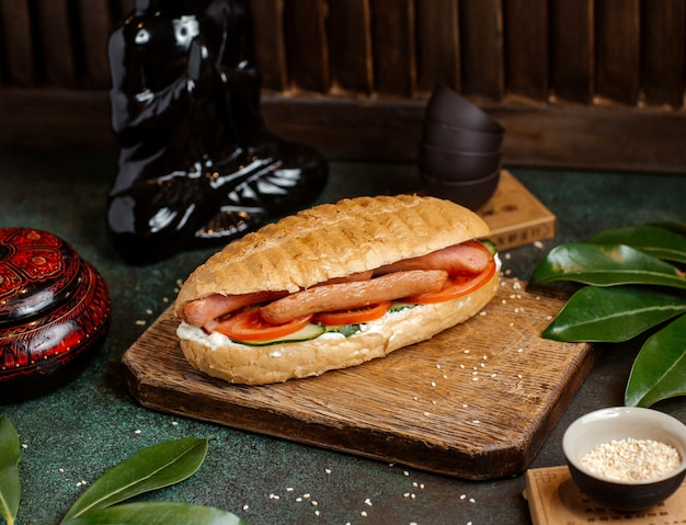 Hotdog bread stuffed with sausages, tomatoes, cucumber and mayonnaise Free Photo