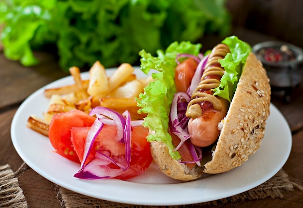 Hotdog with ketchup mustard and lettuce on wooden table. Free Photo