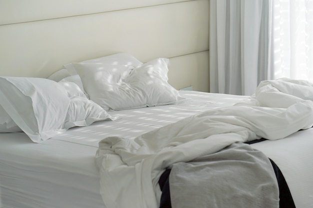 Hotel bed after use. dirty bed pillow blanket room. Premium Photo