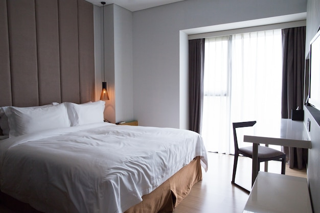 Hotel bedroom with double bed, table and tv set Free Photo