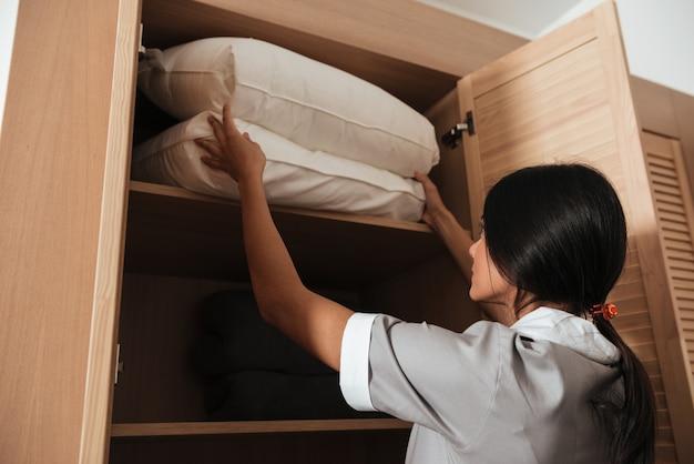 Hotel che fa mettere i cuscini del letto in un armadio Foto Gratuite