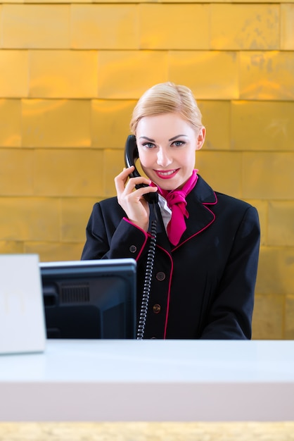 Hotel receptionist with phone on front desk Premium Photo