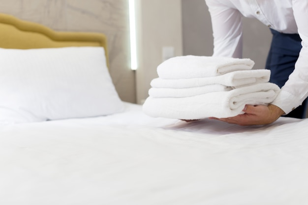 Hotel staff setting up pillow on bed Premium Photo