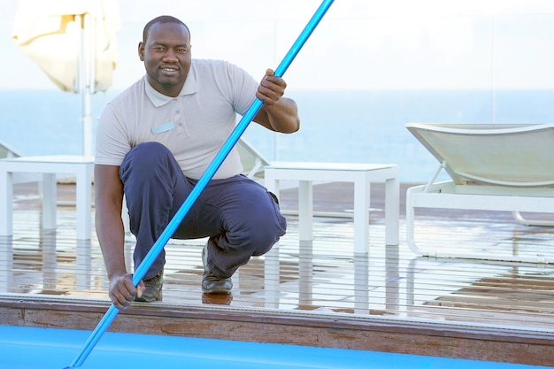 Hotel staff worker cleaning the pool Premium Photo