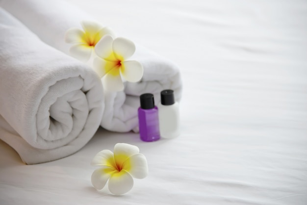 Hotel towel and shampoo and soap bath bottle set on white bed with plumeria flower decorated - relax vacation at the hotel resort concept Free Photo