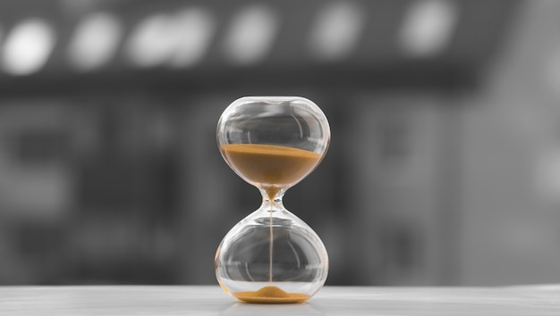 Hourglass on a black and white background of a blurred house, time to buy a home. sand is running out of time. Premium Photo